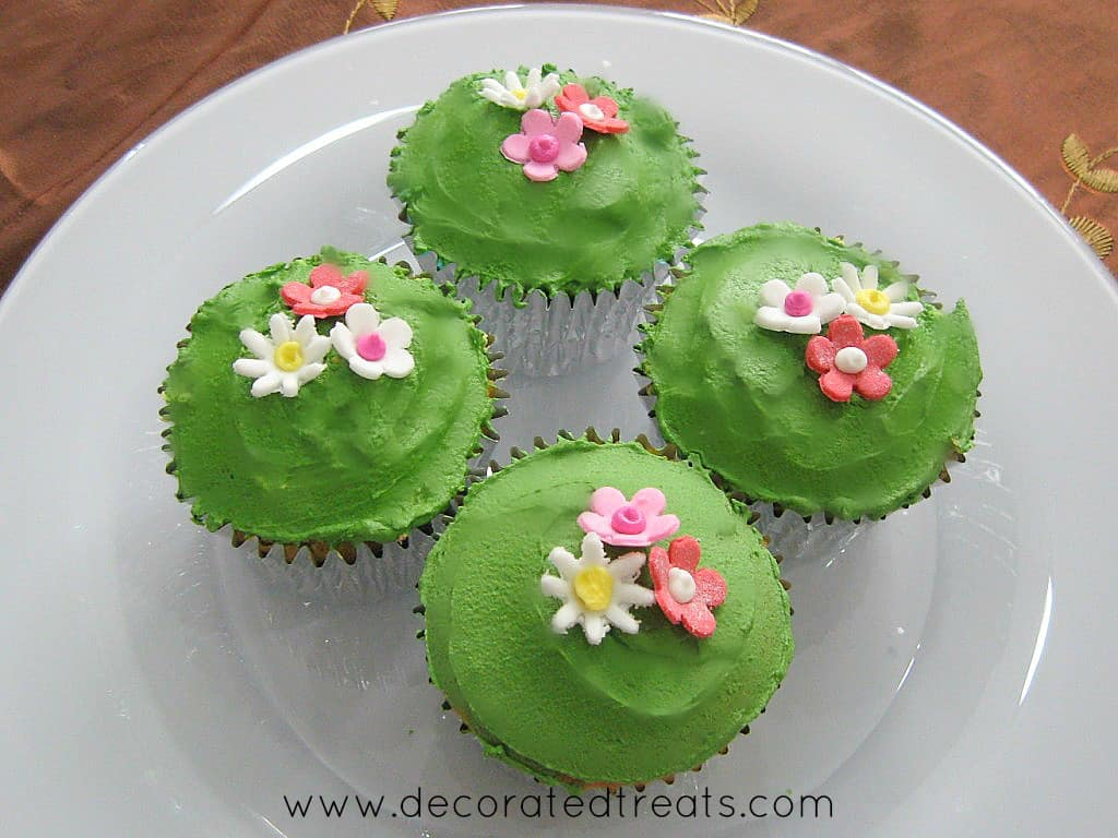 4 cupcakes covered in green icing and decorated with pink and white fondant flowers