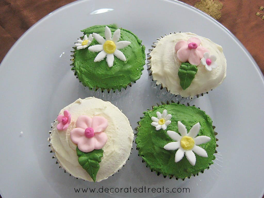 4 cupcakes on a white plate, 2 covered in white icing and pink flowers while the other 2 covered in green icing and decorated with fondant daisies.