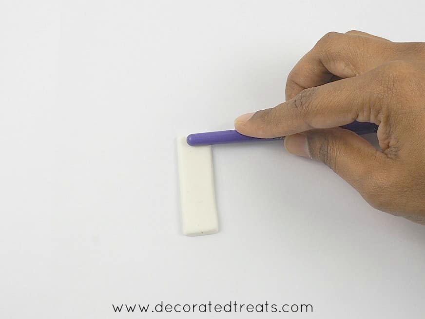 Using the back of a brush to press on fondant