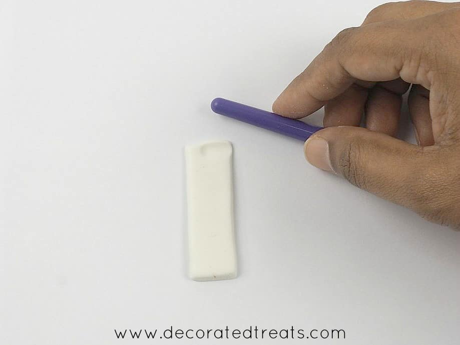 A short white fondant strip with a brush held in hand