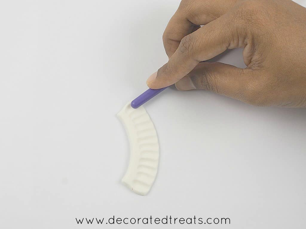 Using the back of a brush to make frills on fondant