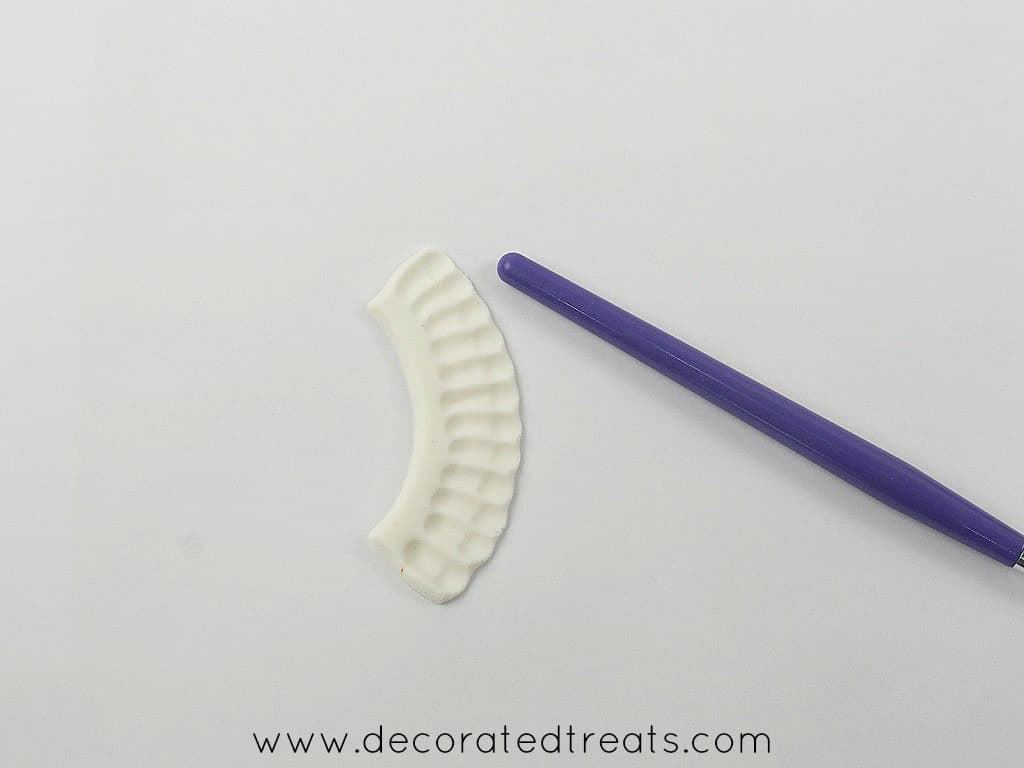 A piece of white fondant frill and a brush
