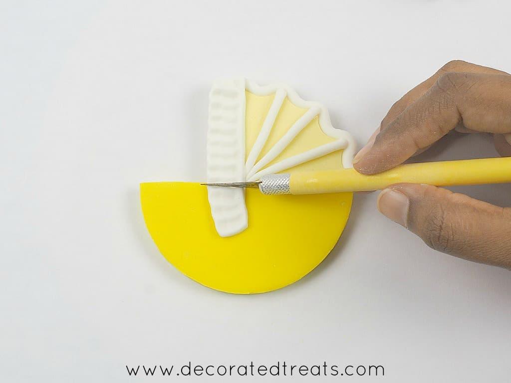 Using a sugar craft knife to cut fondant frills