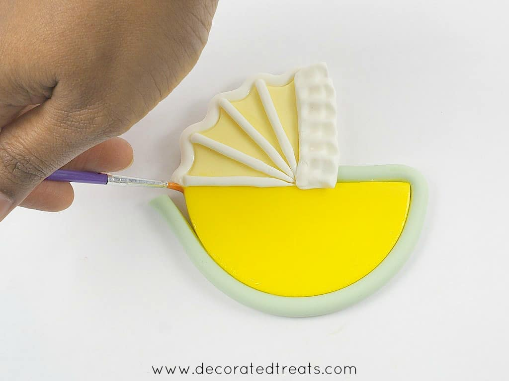Applying glue to fondant with a fine brush
