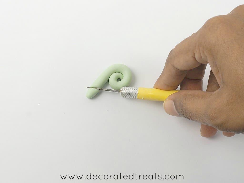 Using a sugar craft knife to cut a piece of green fondant