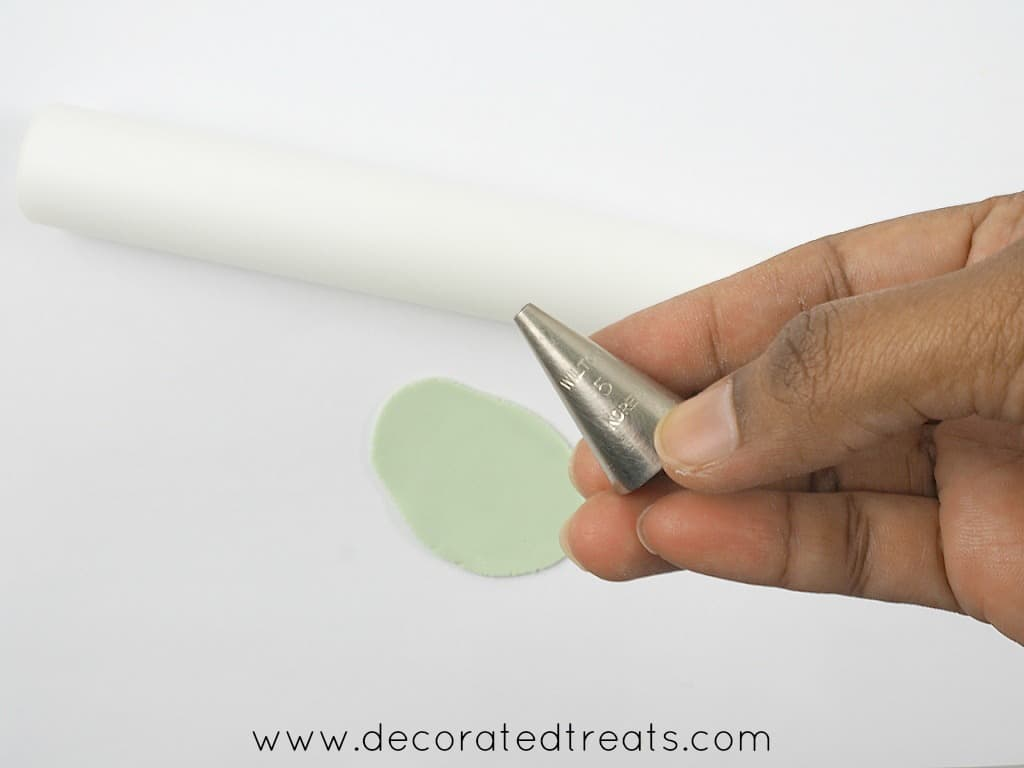 A piping tip with some green fondant and a rolling pin in the background