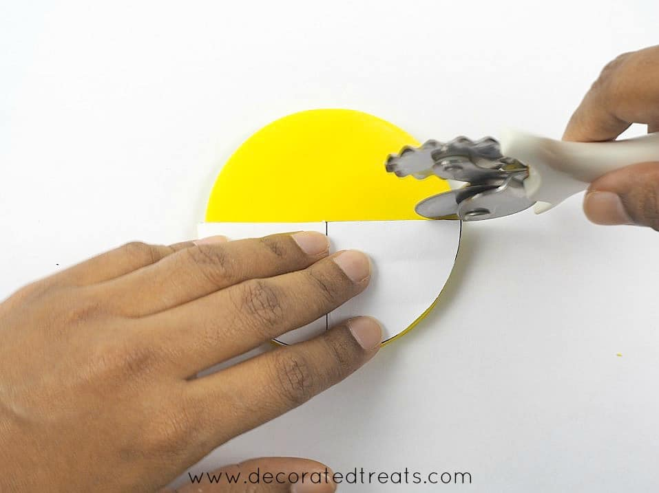 Using a paper template to cut a round fondant into half