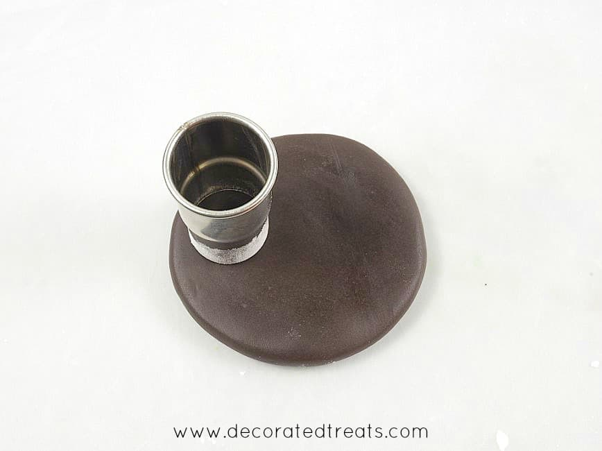 A round cutter on a piece of rolled brown fondant