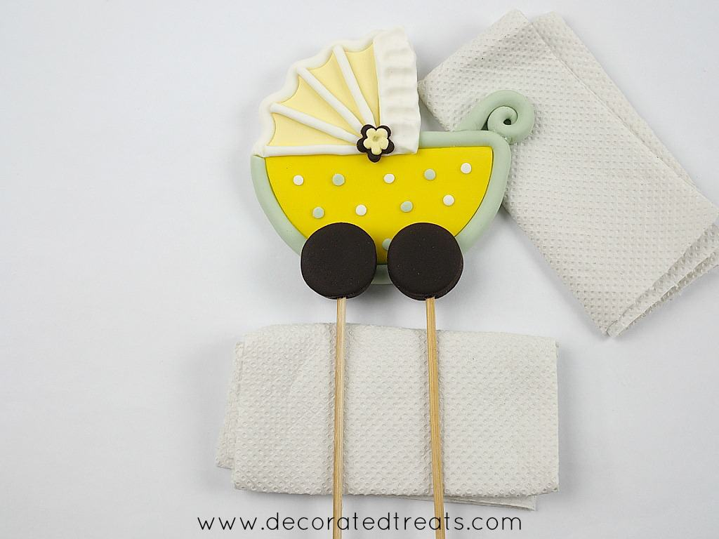 Fondant baby stroller with long skewers attached to the wheels