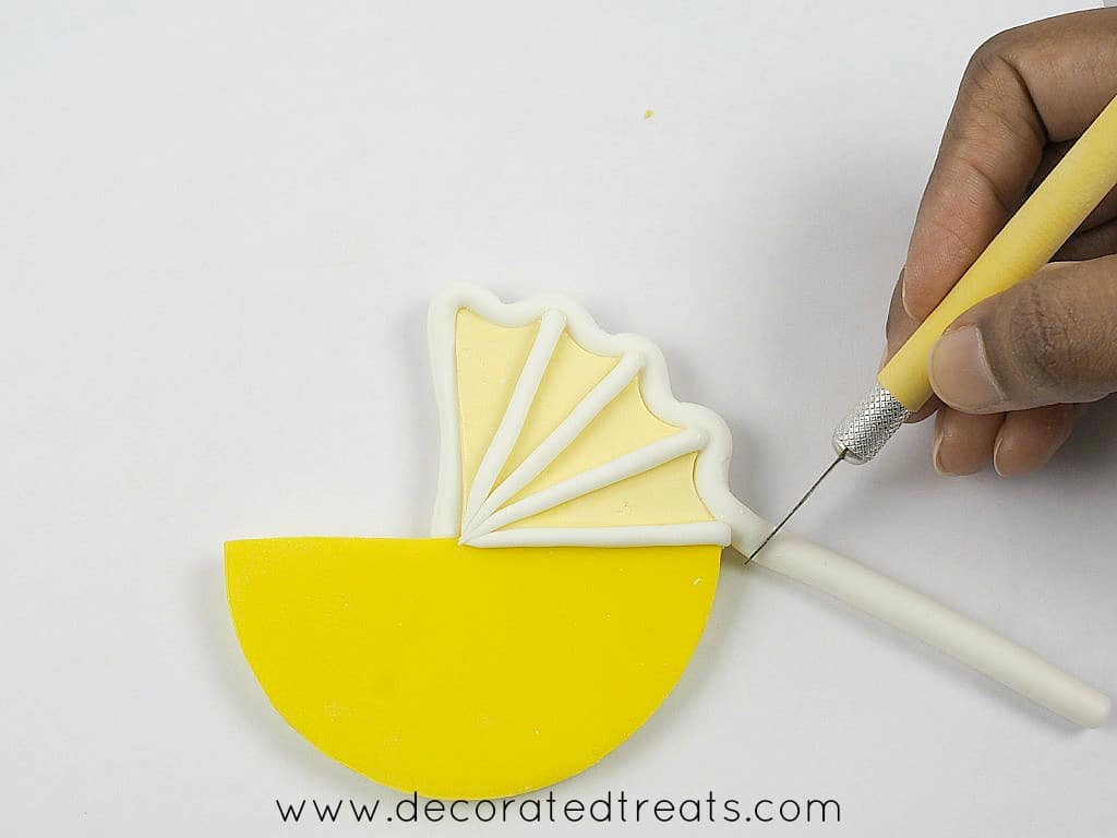 Using a sugar craft knife to cut off excess fondant off a fondant topper