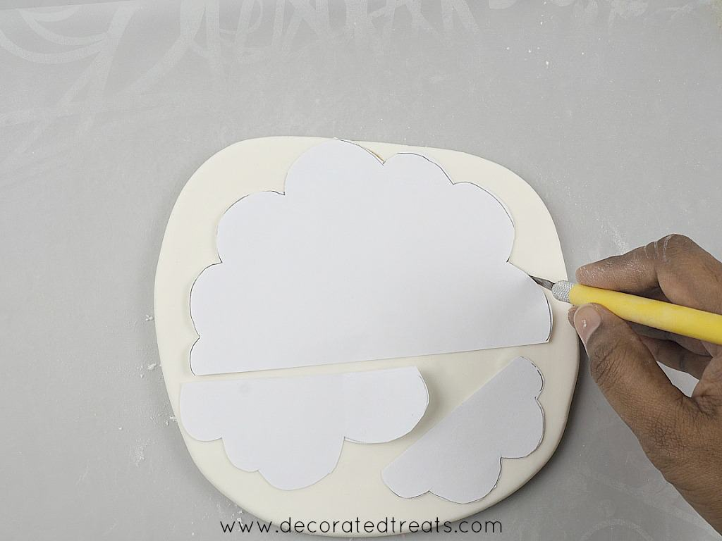 Cloud paper templates on a piece of rolled fondant, and using a sugar craft knife to cut them out