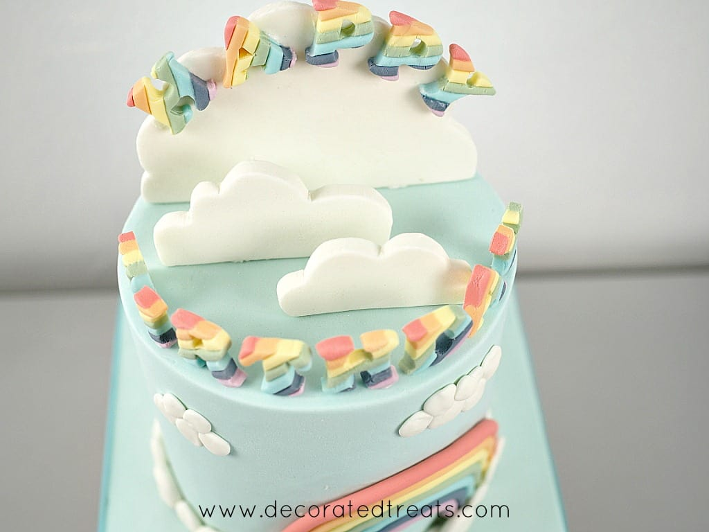 Top of a cake decorated with 3d clouds and rainbow lettering