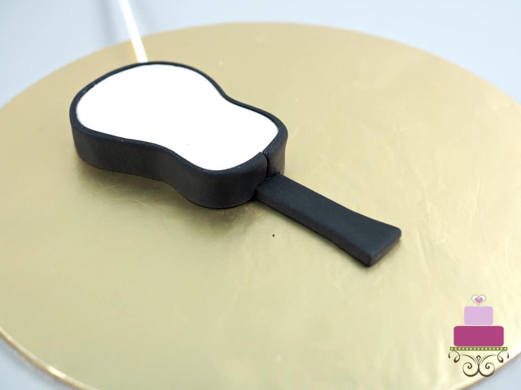 The back of a fondant guitar cake topper
