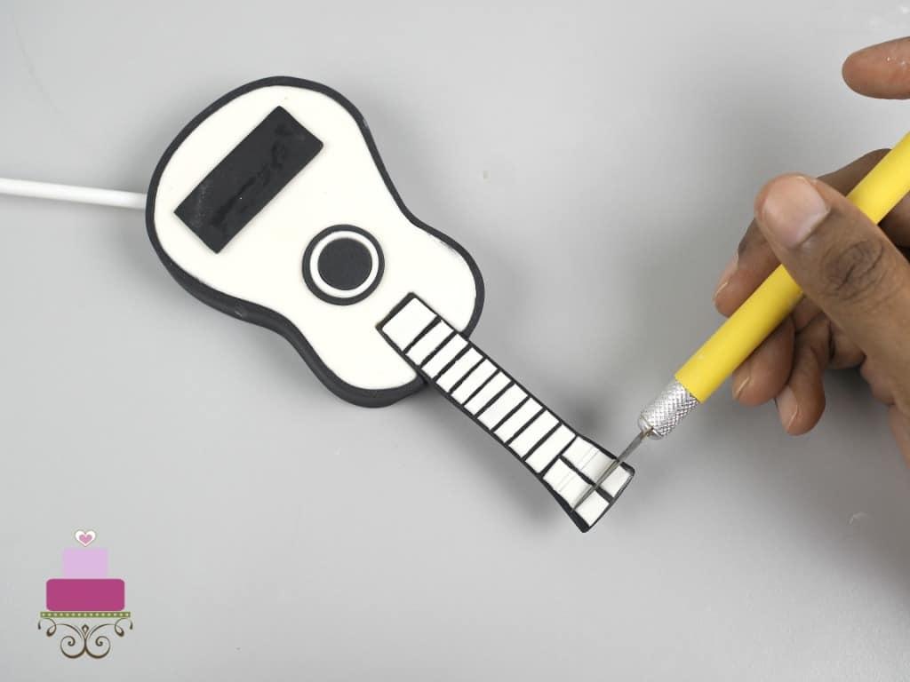 Cutting the fondant guitar top with sugar craft knife