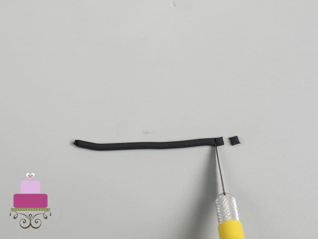 Cutting a strip of black fondant with a sugar craft knife