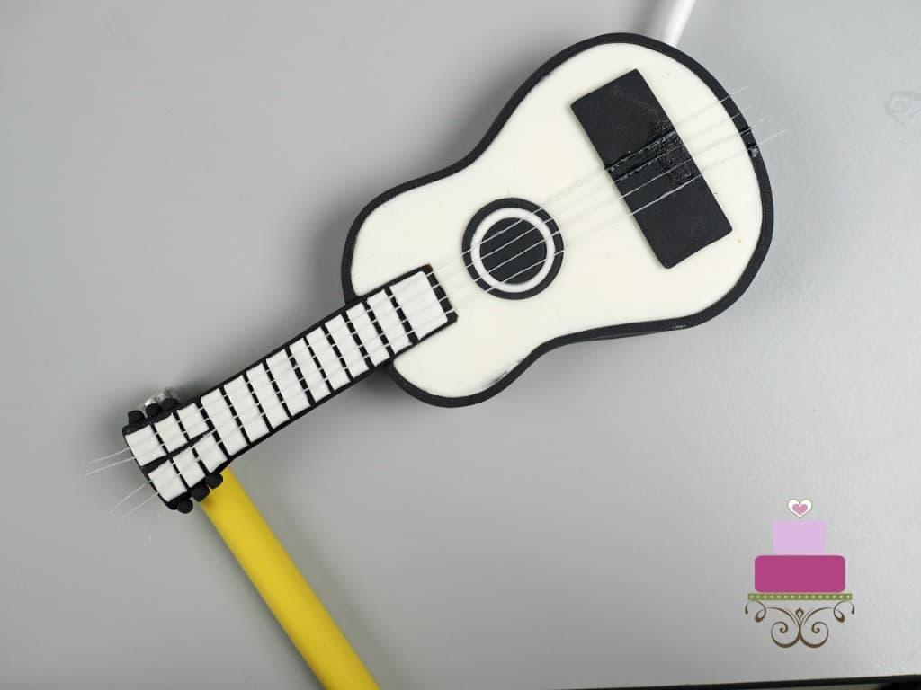 Fondant guitar cake topper resting on a yellow stick