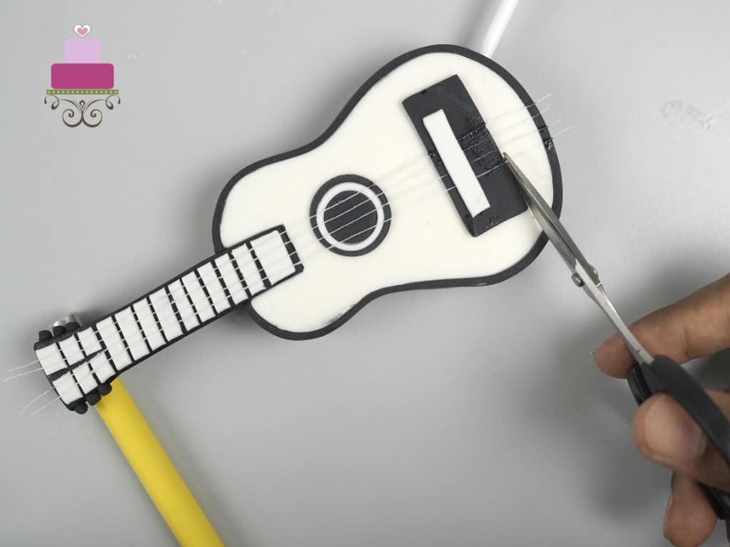 Cutting off excess thread on the fondant guitar cake topper