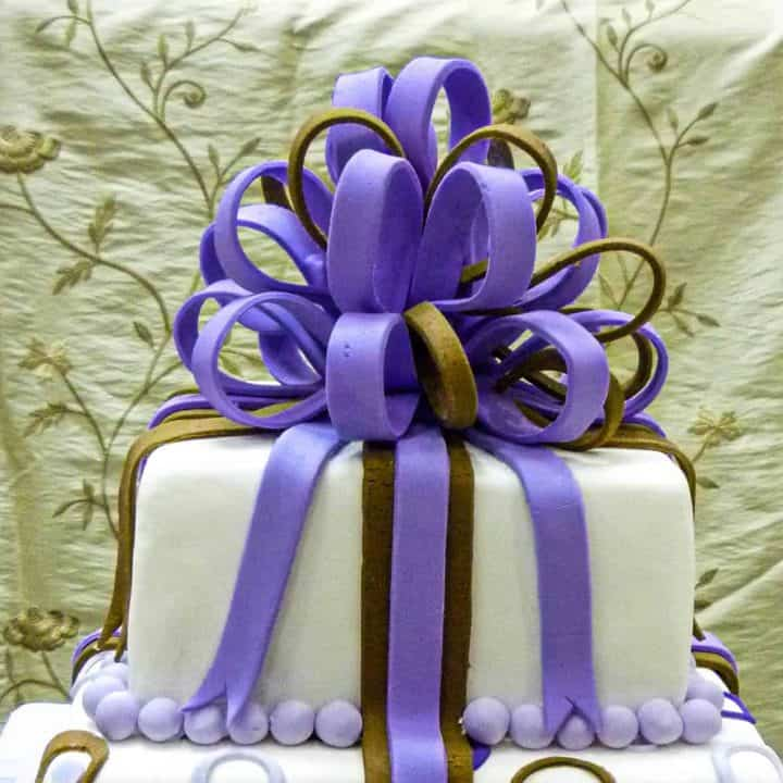 A violet and brown fondant loop bow on top of a 2 tier square cake