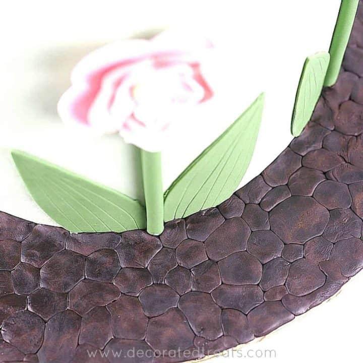 Brown fondant pebbles effect on cake board
