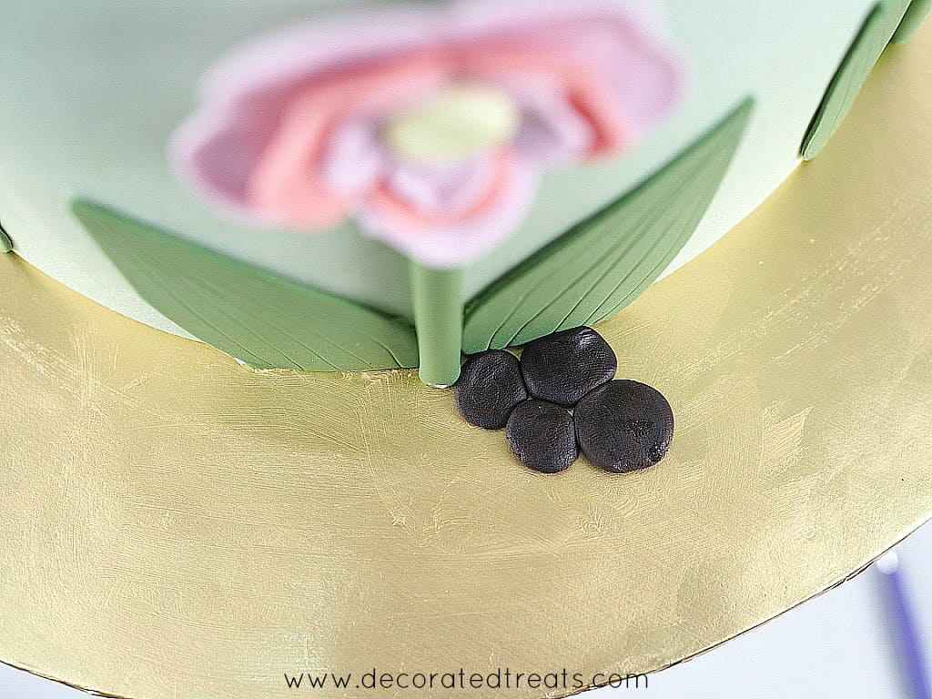 4 small pieces of flat, brown fondant on a gold cake board