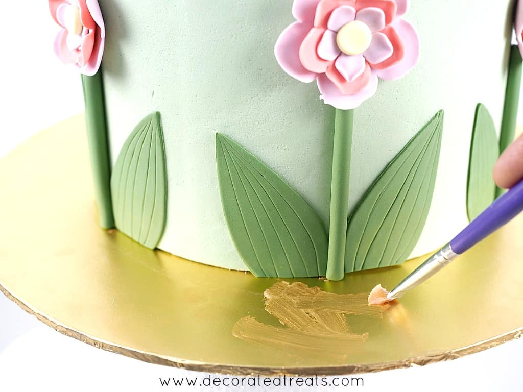 Applying shortening to the cake board with a brush