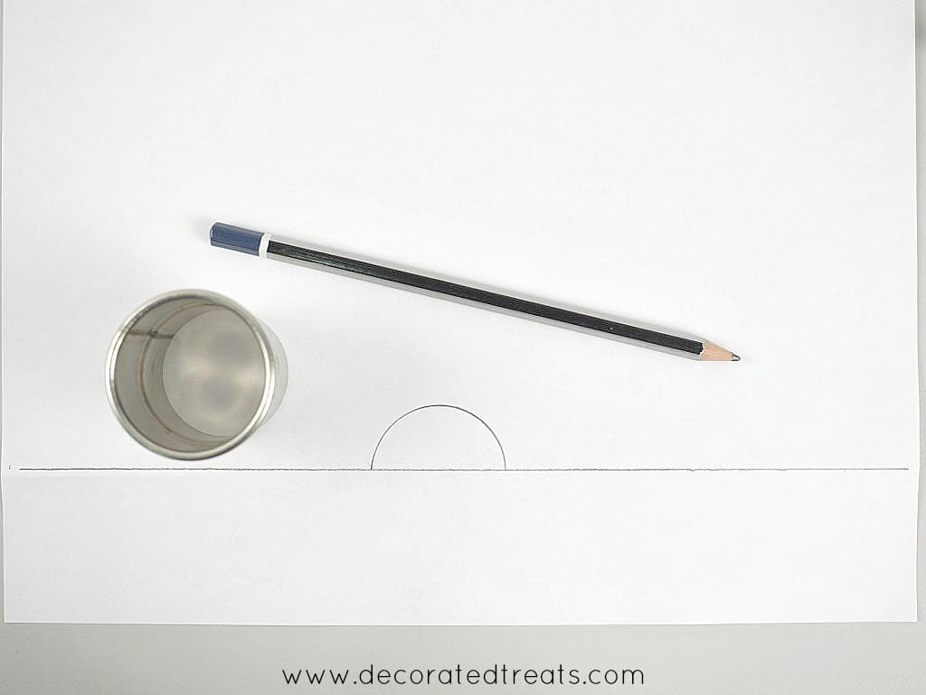 A paper with a semi circle drawn on it. In the background are a round cutter and a long pencil