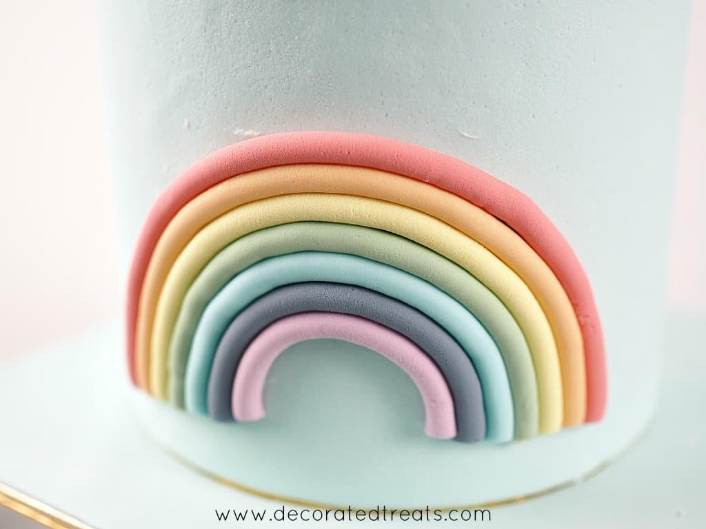Fondant rainbow on the side of a light blue fondant covered cake