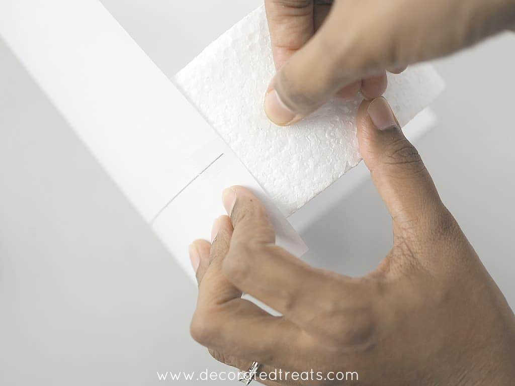 Attaching a paper to a styrofoam dummy with tape