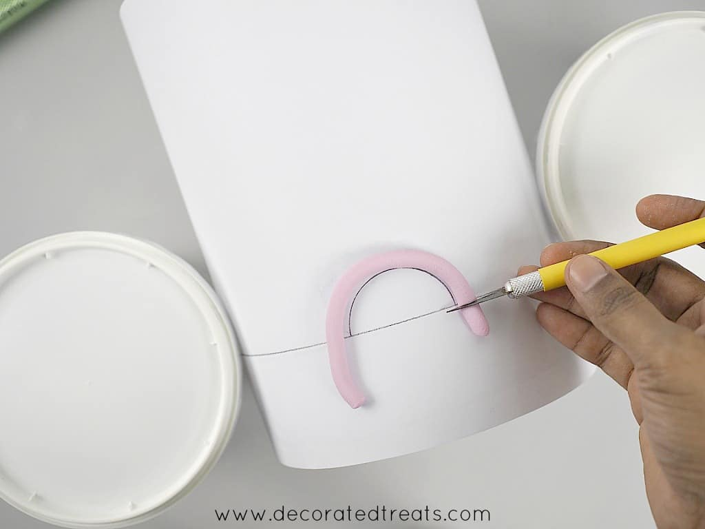 Using a sugar craft knife to cut the excess of a violet strip of fondant