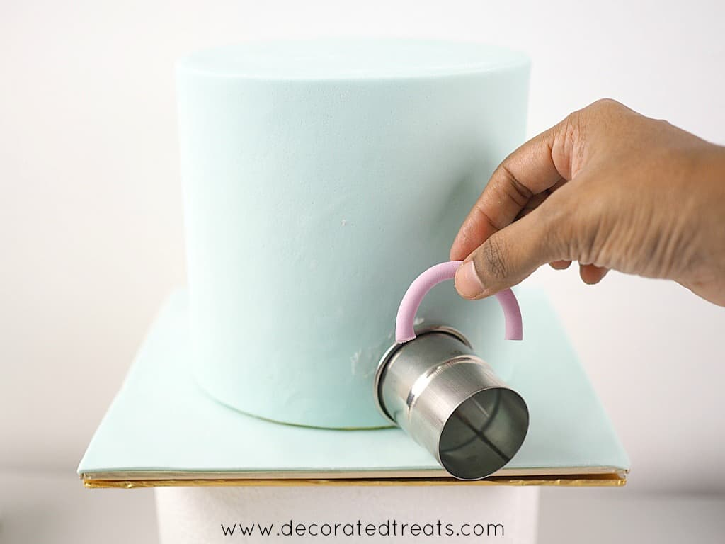 A semi circle strip of violet fondant held in hand. In the background is a blue cake with a round cutter on the side.