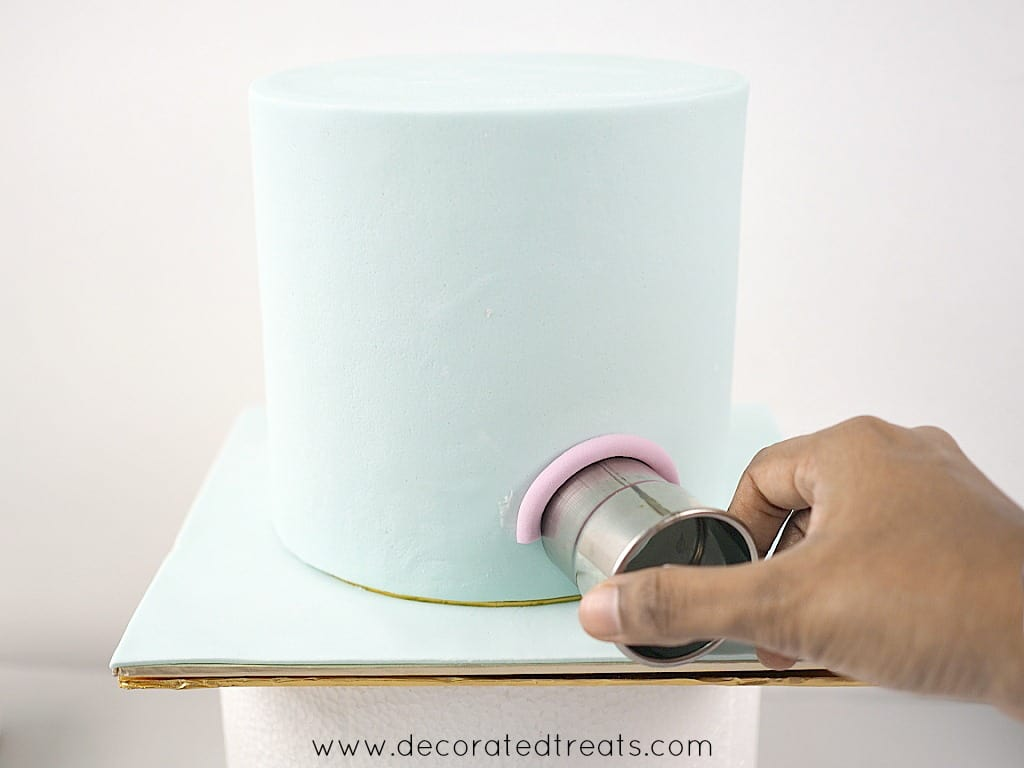 Using a round cutter to position a violet fondant strip on the side of a cake