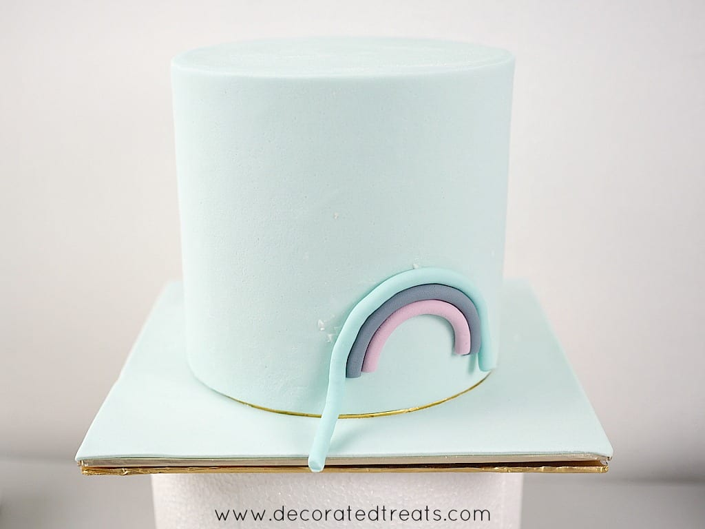 Blue, violet and indigo fondant strips in the shape of a rainbow on the side of a blue fondant covered cake