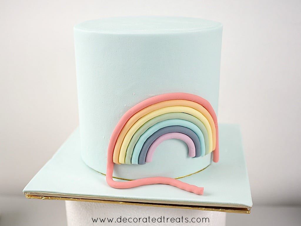 Fondant rainbow on the side of a light blue fondant covered cake. The red strip of the rainbow is longer than the rest of the colors