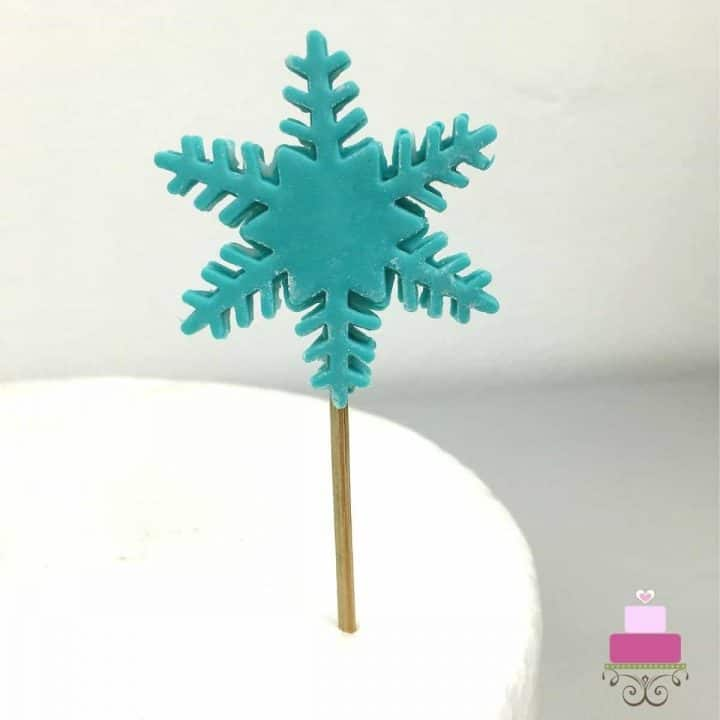 A snowflake fondant cut out with a toothpick attached