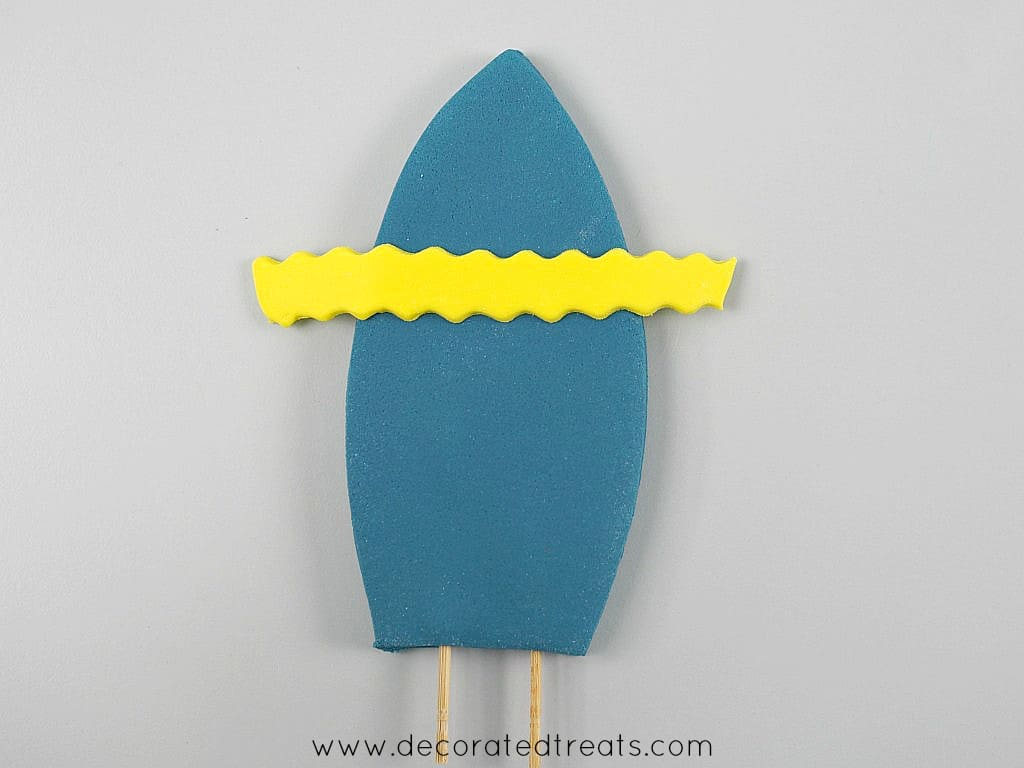 A yellow fondant strip placed horizontally on a blue surf board shaped fondant cut out