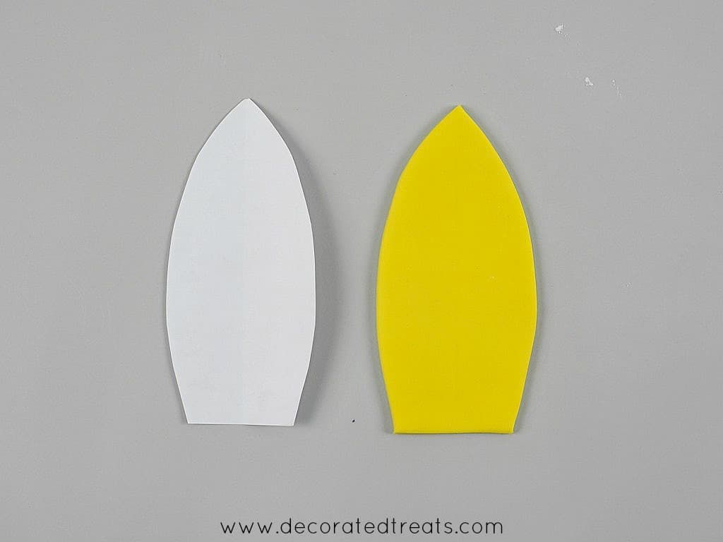 Fondant cut out and paper template in the shape of a surf board