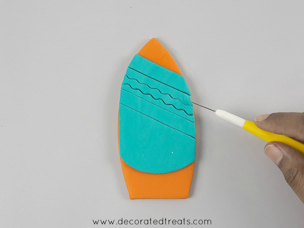 Using a needle tool to remove fondant stripes on an orange surf board shaped cut out