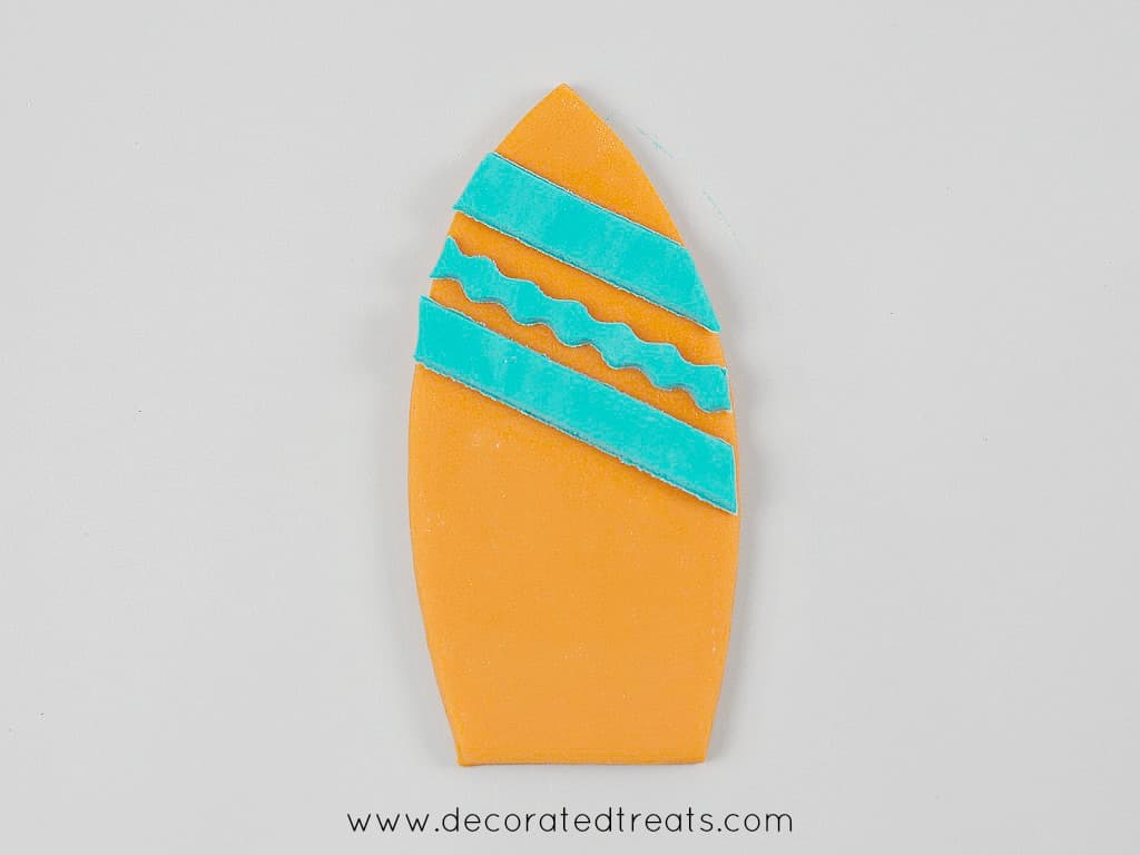 Fondant cut out in the shape of a surfboard in orange with blue stripes