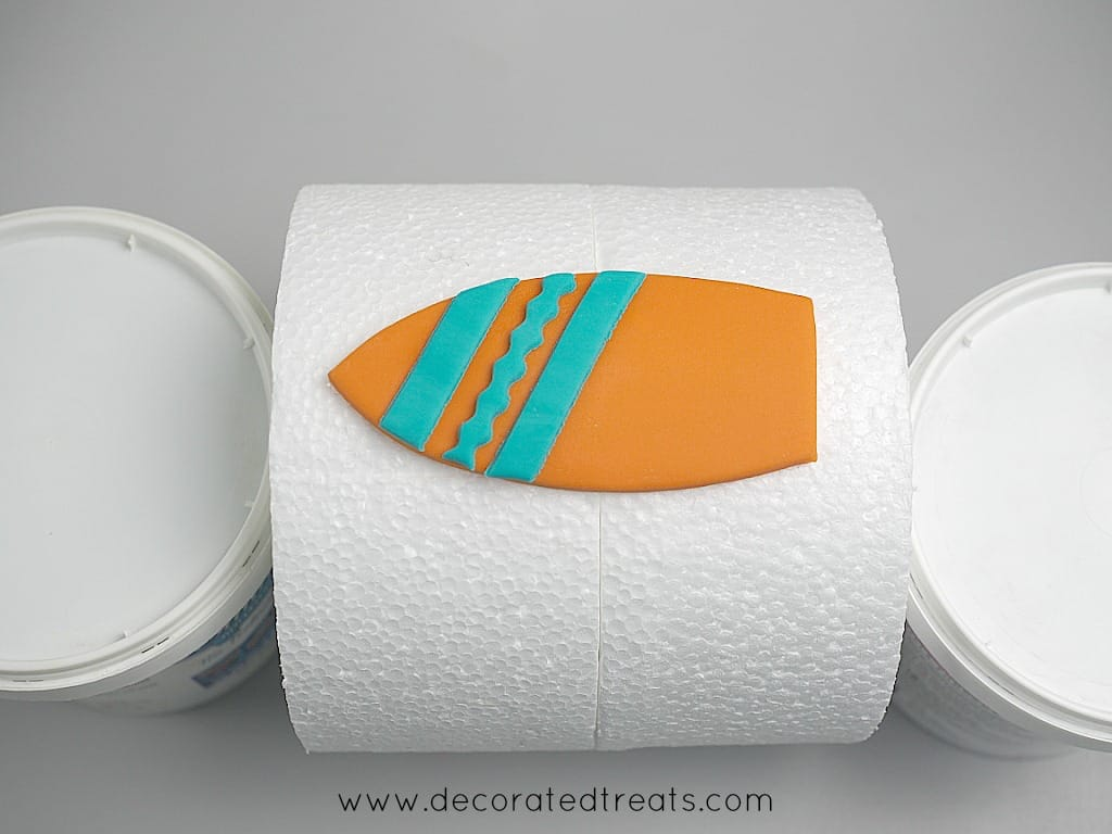 Fondant cut out in the shape of a surfboard in orange with blue stripes, on a the sides of a styrofoam dummy