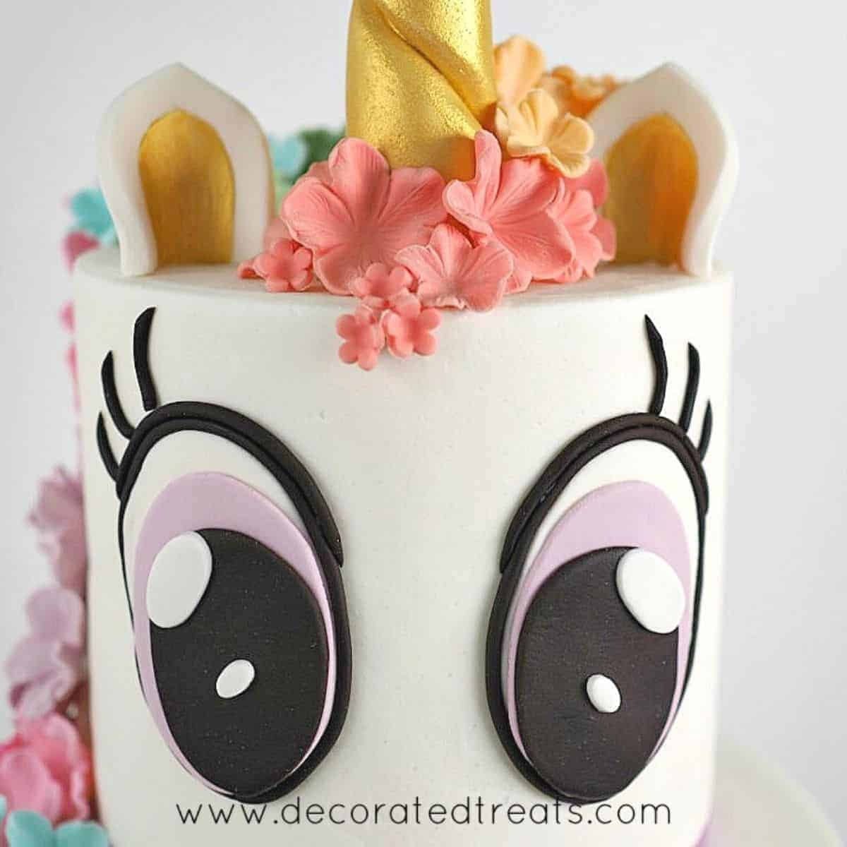 A two tier white unicorn cake with 2 large fondant eyes on the top tier
