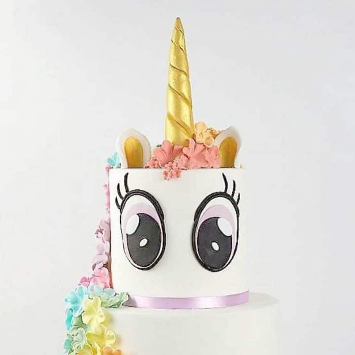 A two tier unicorn cake with eyes and golden horn
