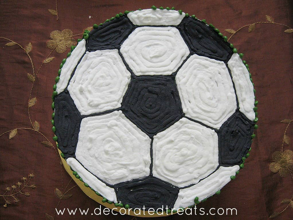 A round cake with the top decorated in a black and white football
