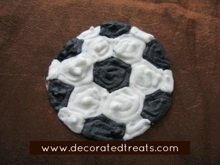 A royal icing piped soccer ball on brown background