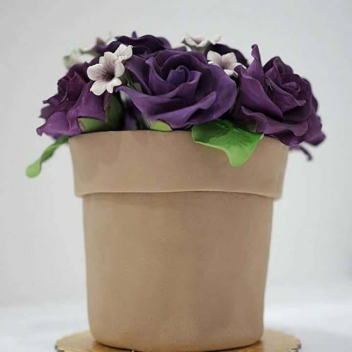 A flower pot cake with purple gum paste roses