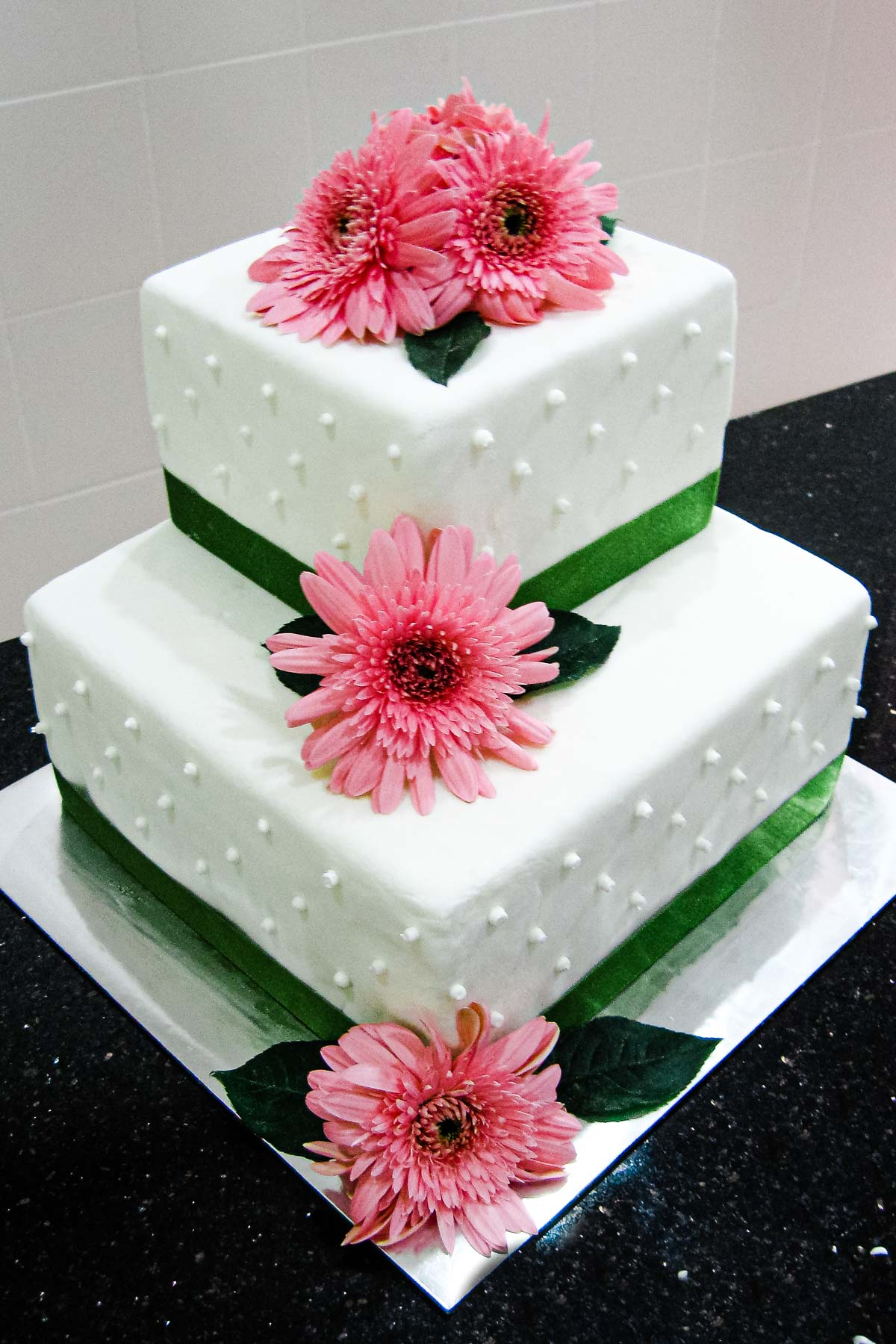 2 tier white square wedding cake with pink gerbera daisies and green ribbon border