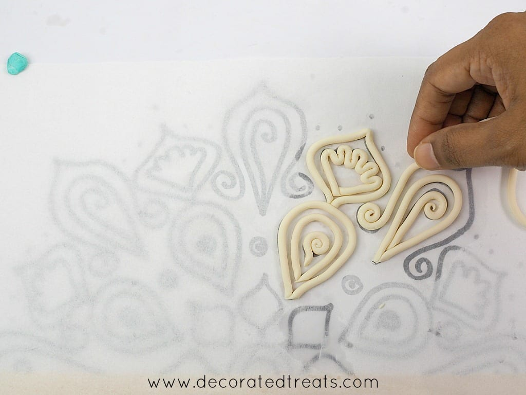 Arranging fondant strips arranged on lace paper template