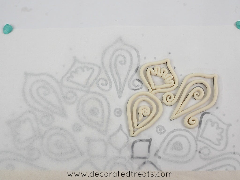 Fondant strips arranged on lace paper template