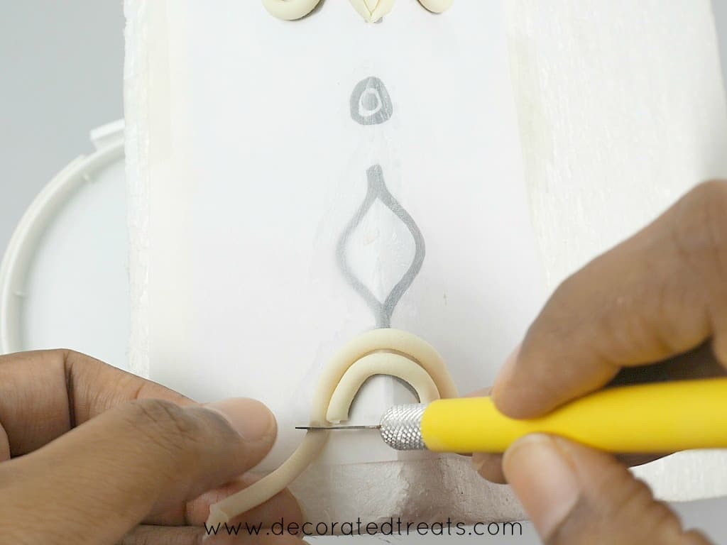 Using a sugar craft knife to cut excess fondant of a paper lace template