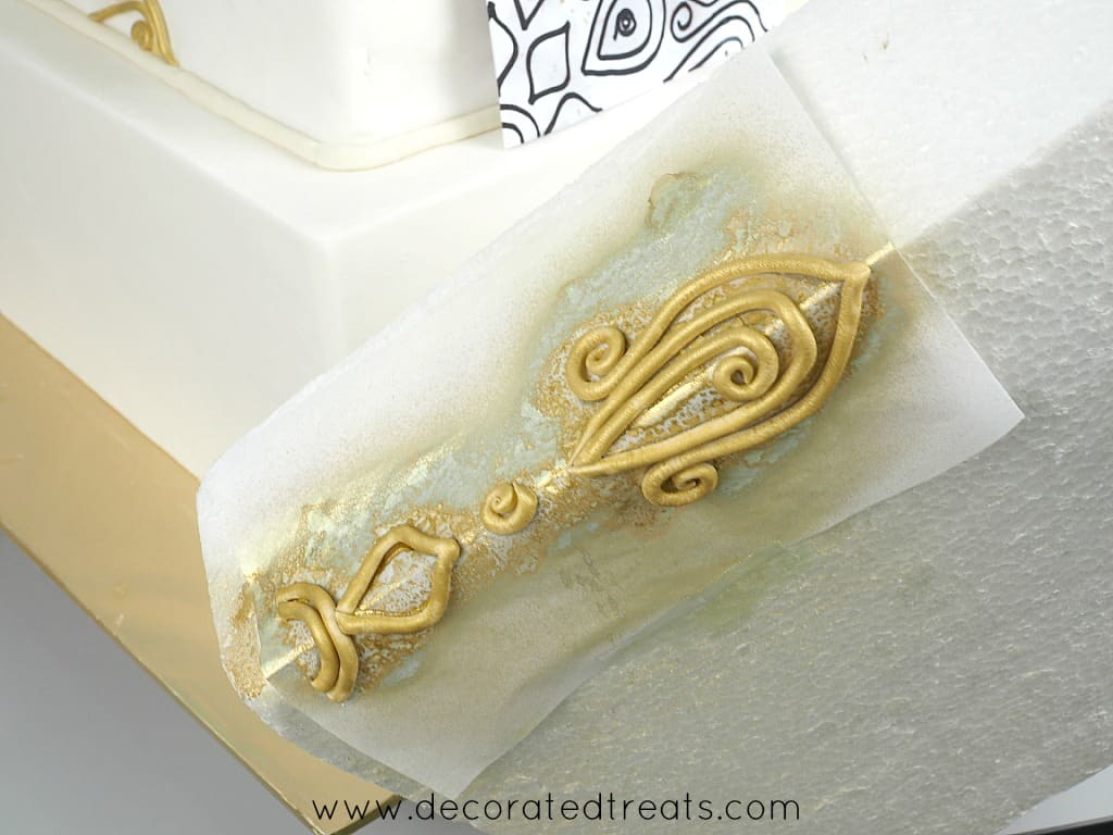 Gold fondant lace on a paper template