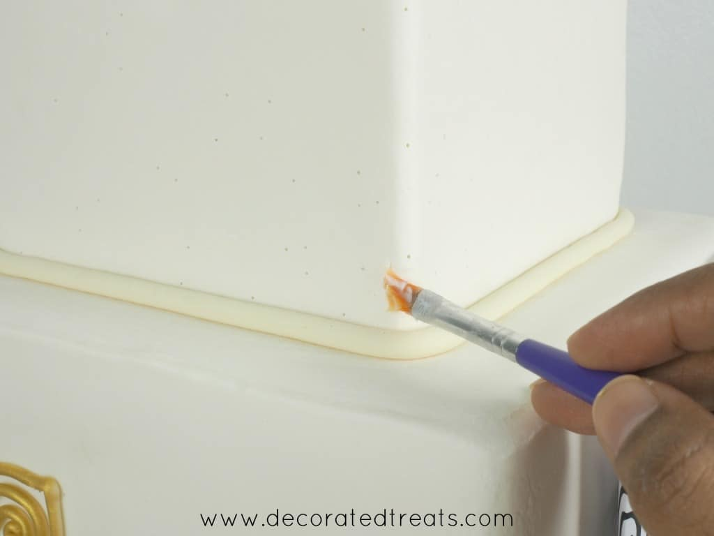 Using a purple brush to brush on a fondant covered square cake